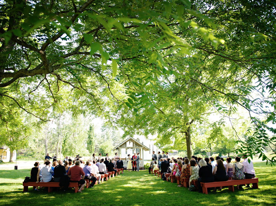 outdoor wedding venue with many chairs filled with guests and bride and groom in the centre going through ceremony on a bright day
