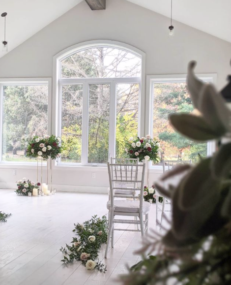 interior of a wedding venue with many white pieces of decor and large floral arrangements throughout