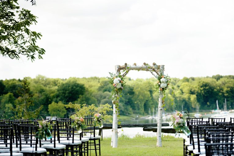 outdoor wedding ceremony area with floral covered arch way and black and white ceremony chairs looking towards the water