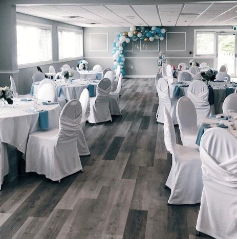 interior of a wedding venue with white covered chairs with blue accents throughout the room with tables set for dining