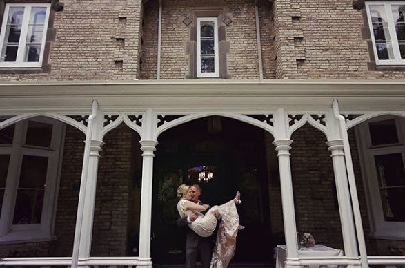 exterior of a building with a man picking up a woman in a wedding dress and kissing her cheek