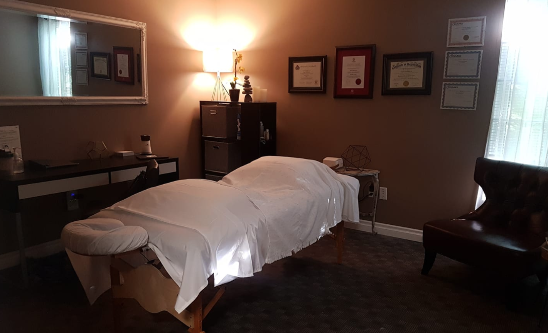 interior of a massage room with dim lights and various certifications hanging on the wall
