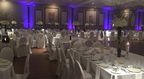interior of a wedding venue with tables set for dinner with white decor and purple lighting towards the head table in the background