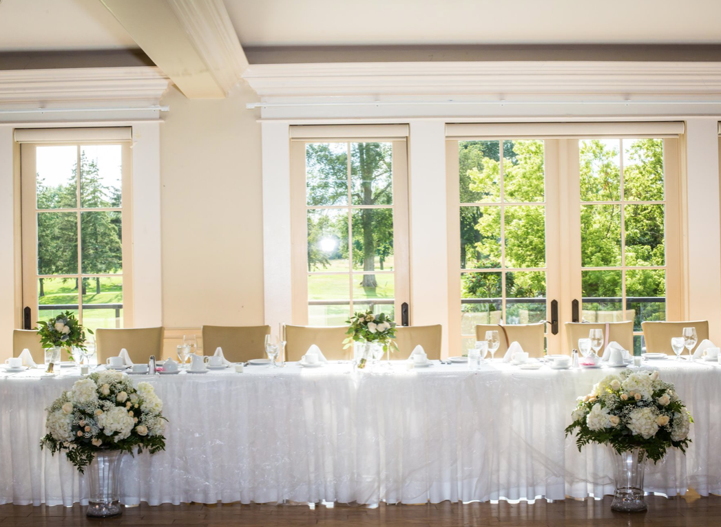 interior of a wedding venue with view of the head table set for dinner with white linens and decor with large flower arrangements in front of the table against a window on a bright day