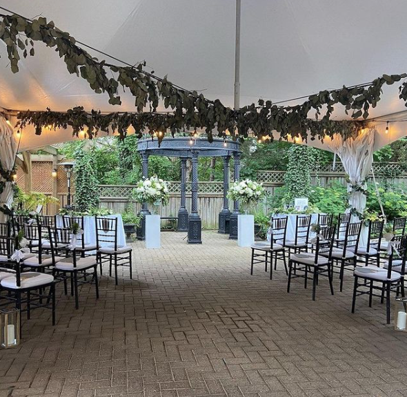 wedding ceremony set up with black and white chairs under a tent and foliage hanging from the top of the tent