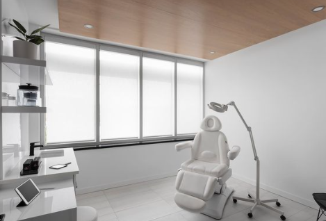 interior of a spa medical room mainly white with patient chair in the centre of the room with open blinds