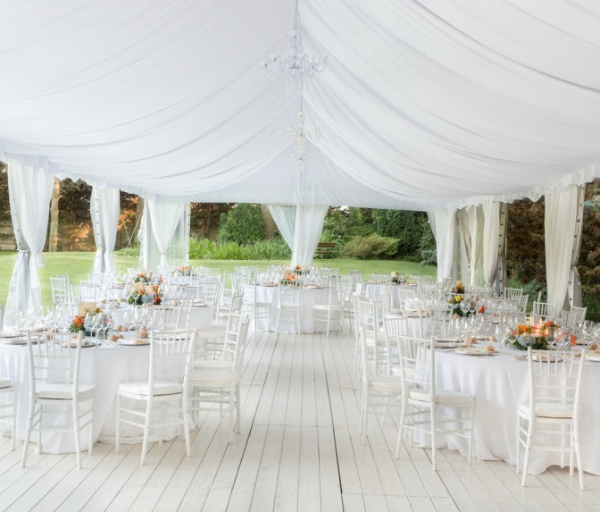 wedding dinner area outdoors under a white tent with many pieces of white decor and orange coloured flower arrangements in the centre of each table