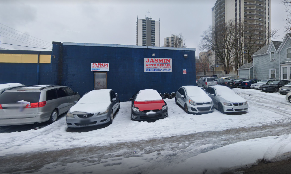 exterior of a blue auto mechanic building in the winter with cars parked out front with snow on them