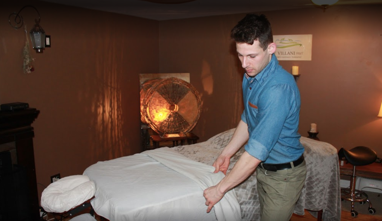 interior of a massage room with a made bed with man pulling up a sheet