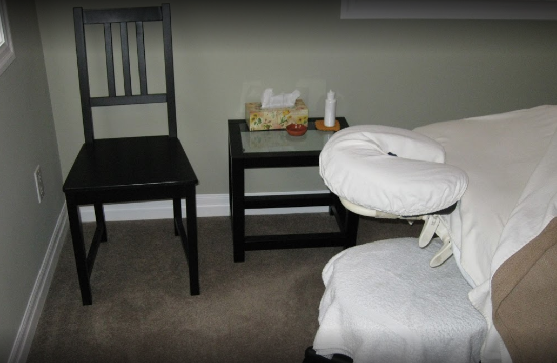 interior of a massage room with a made bed and lotion sitting on a table
