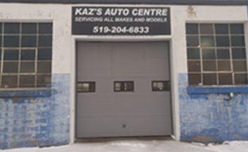exterior of an auto mechanic with one garage door and branded sign sitting on top
