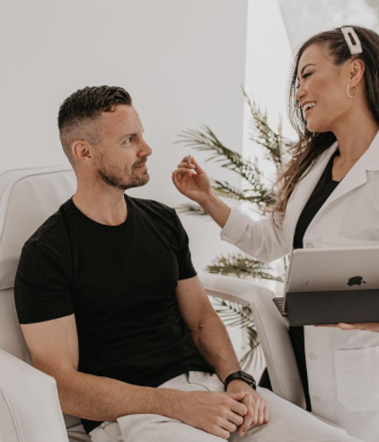woman smiling at man in a patients chair holding an ipad