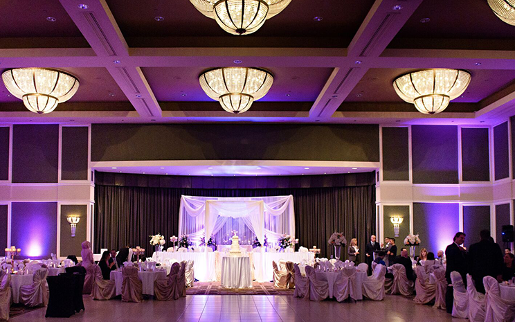 interior of a wedding venue with view of dance floor and tables set for dinner looking towards head table with purple lights in behind
