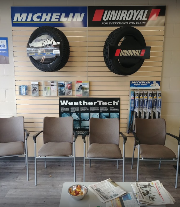 interior of a mechanic waiting room with four chairs in a line and car accessories in behind with two tires mounted on the wall