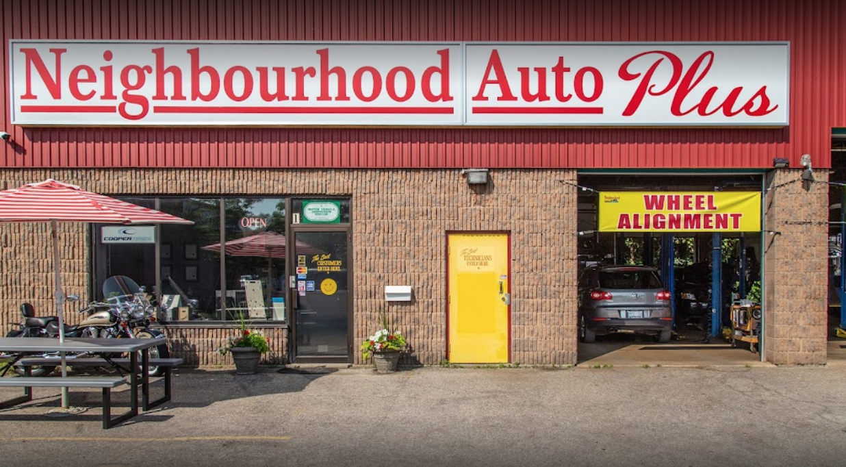 exterior of an auto mechanic with a picnic table to the left and garage door to the right with entrance in between