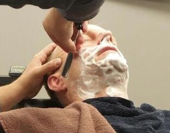 man getting a shave in a barber shop