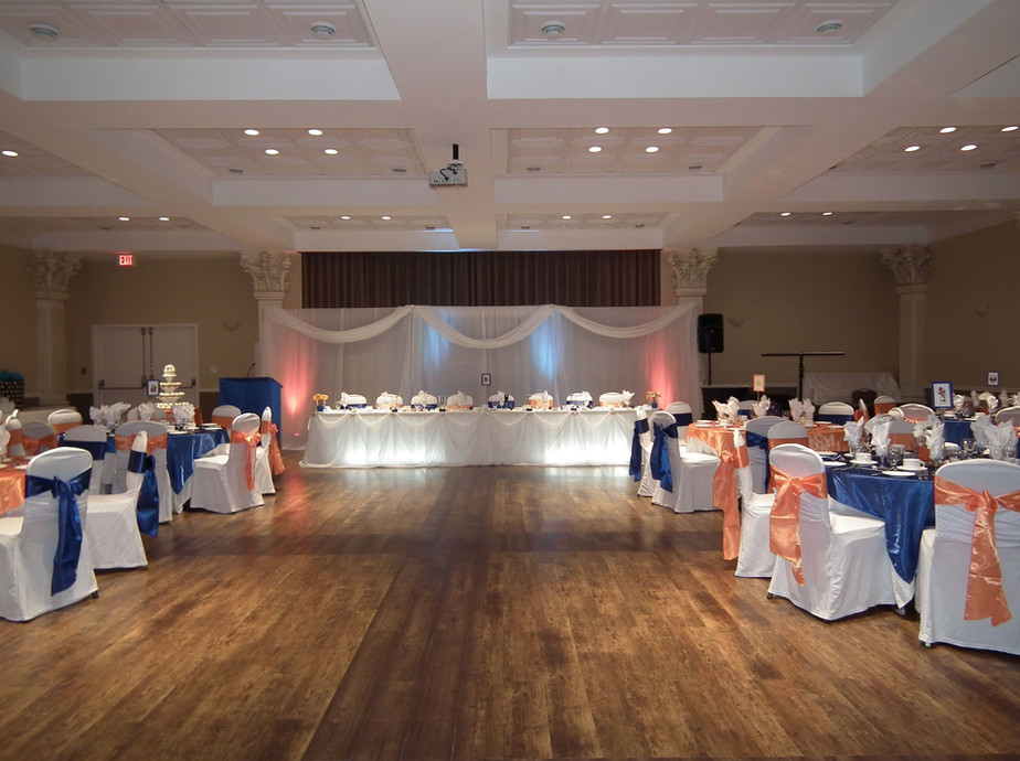 interior of wedding venue with tables set for dinner with blue and orange accents looking at head table with blue and orange lights in behind