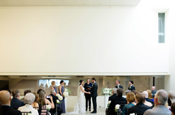 wedding ceremony with bride and groom holding hands in the middle of the room and guests sitting in chairs