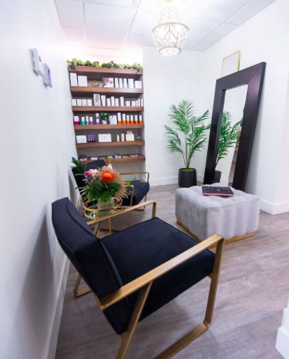 waiting room with two large black chairs facing a mirror with shelving in behind filled with nail polish and different skincare products