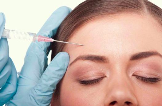 gloved hand inserting a syringe into a womans forhead who has her eyes closed against a white background