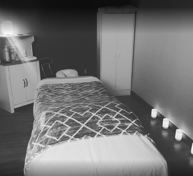 interior of a massage room with a made bed with candles lit and a small shelf with lotions and other massage accessories (black and white photo)