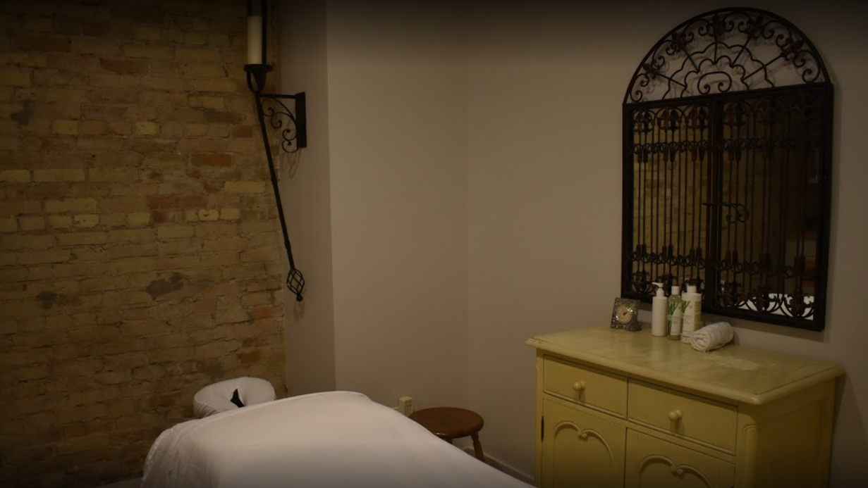 interior of a massage room with a made bed beside a table with various lotions on top