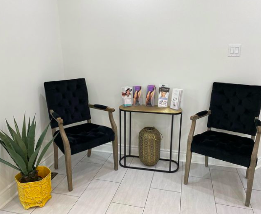 reception area with two black chairs and a table with brochures in the middle
