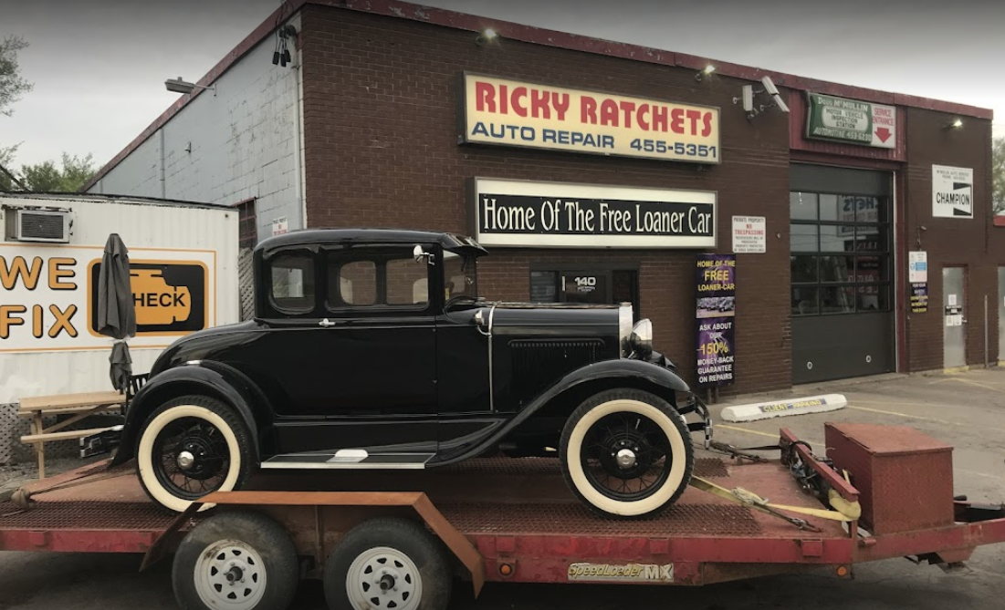 exterior of an auto mechanic with an old style car sitting on a trailer with a garage door to the right