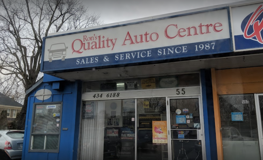 exterior of an auto mechanic with large sign on top and front glass windows and doors