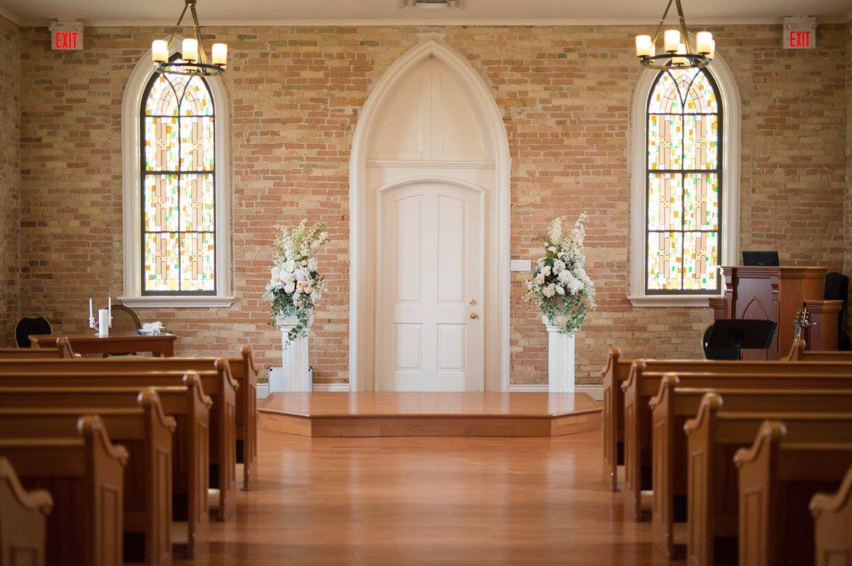 interior of a wedding venue with a small platform for couple in front of an arched door with church pews