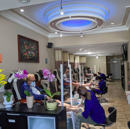 interior of a spa with many pedicure tables in a row and people wearing blue scrubs working on feet