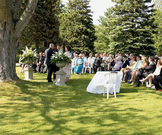 outdoor wedding ceremony with the couple in the centre and many guests looking towards them on a bright day