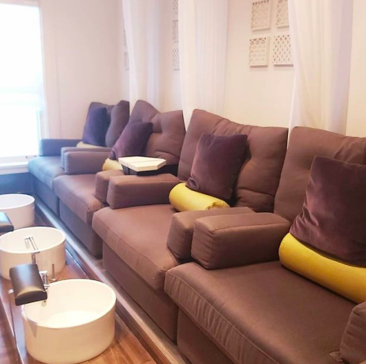 set of four brown lounge chairs with purple and yellow pillows with tubs for pedicures in front
