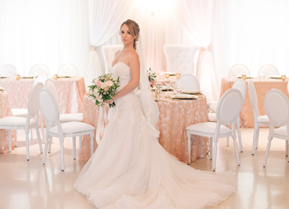 woman standing in a wedding dress holding a bouquet of flowers in a white and pink decorated dining area on a bright day