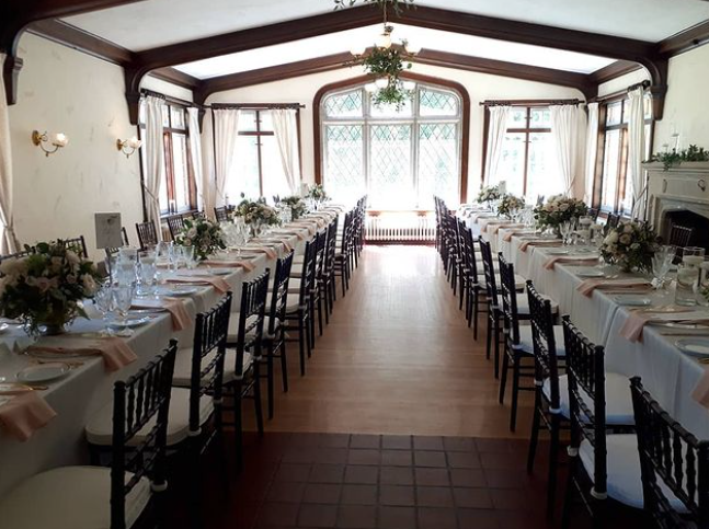 interior of a wedding venue with two long tables set up for dinner with pink accents in front of a window on a bright day