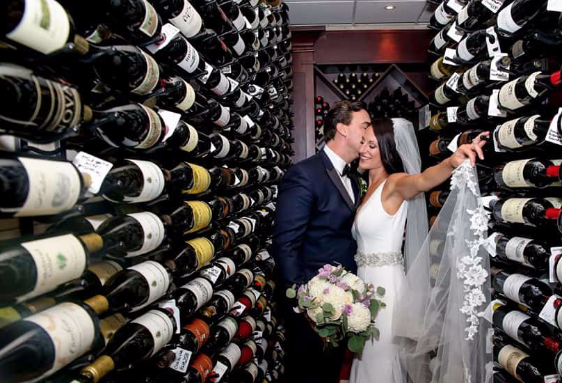 recently married couple inside a wine cellar with her hand grabbing the wall and him kissing her on the cheek