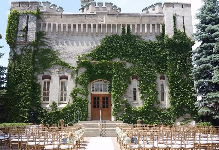 old style building with ivy growing on the walls with many wedding ceremony chairs set up and floral arrangements on the end of each row