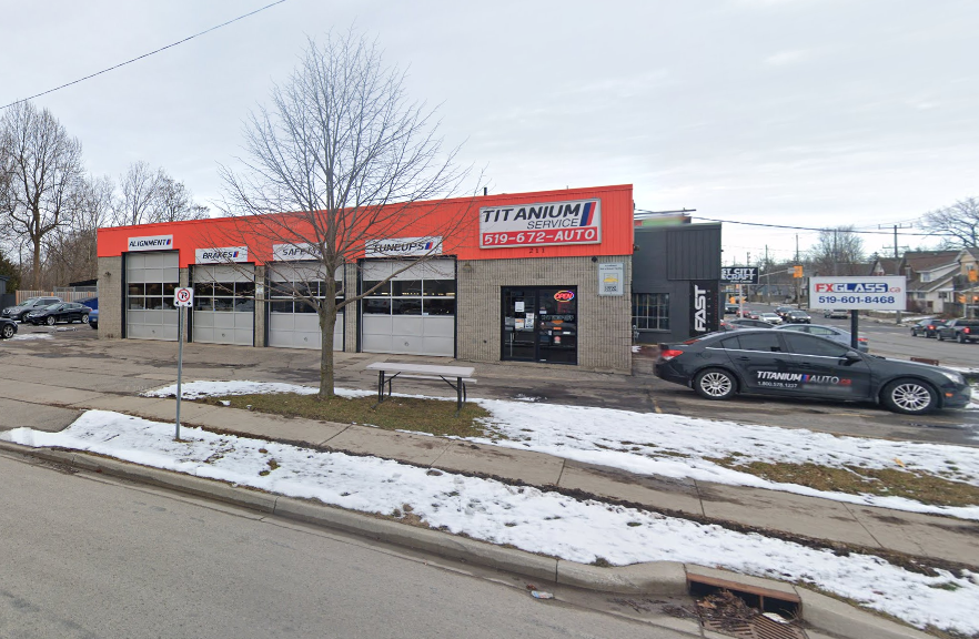 exterior of an auto mechanic with orange trim around the roof and four garage doors with entrance to the right and a car sitting in the parking lot