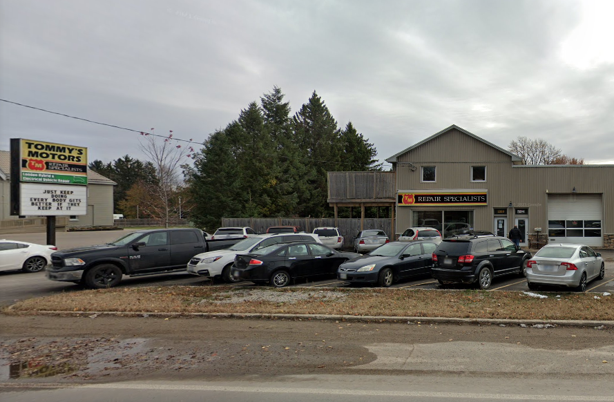 exterior of auto mechanic with many cars in the parking lot blocking view of the building