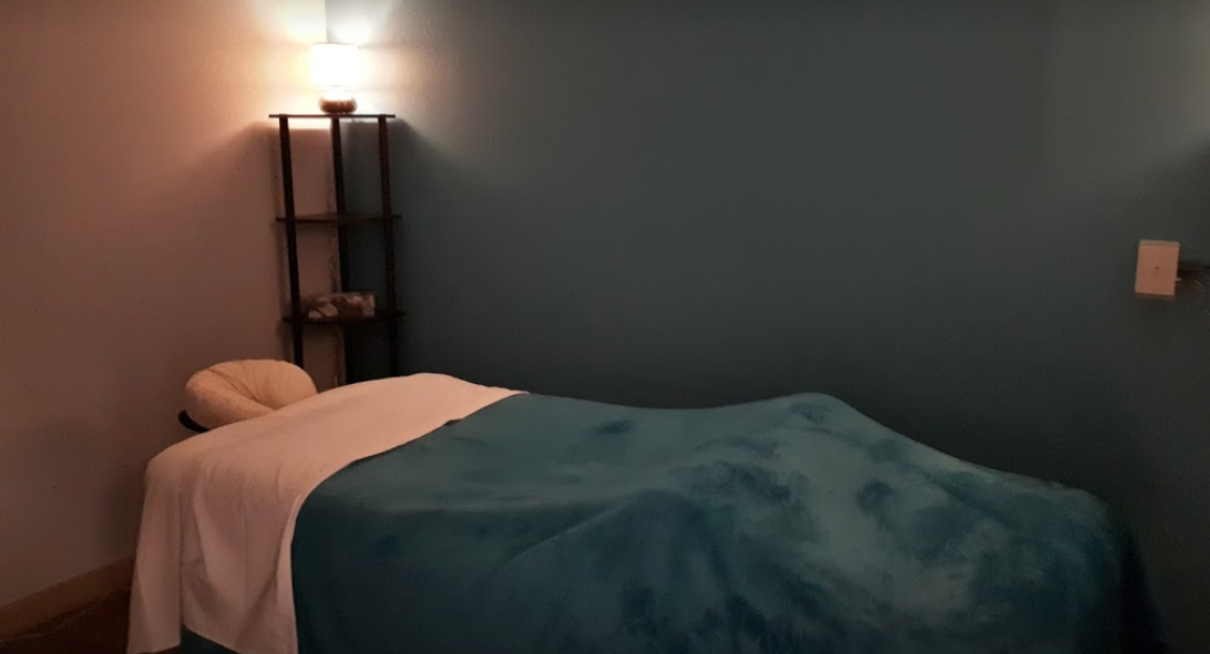 interior of a massage room with a made bed beside a shelf with lotions