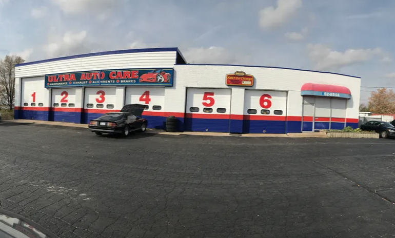 exterior of an auto mechanic with six garage doors all closed with one car sitting with hood open in front of garage door