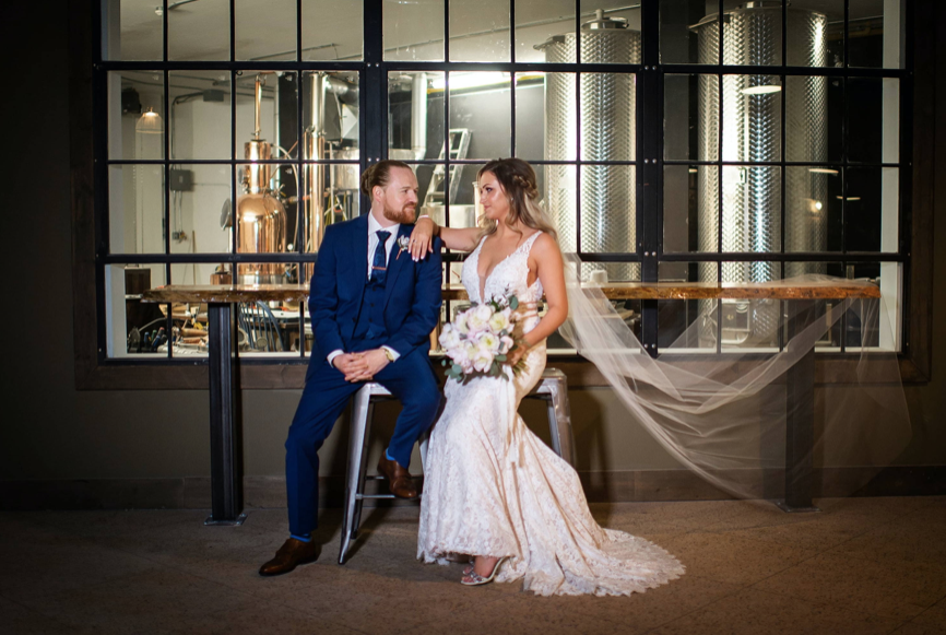 recently married couple looking at each other with her hand hanging off his shoulder in front of a distillery