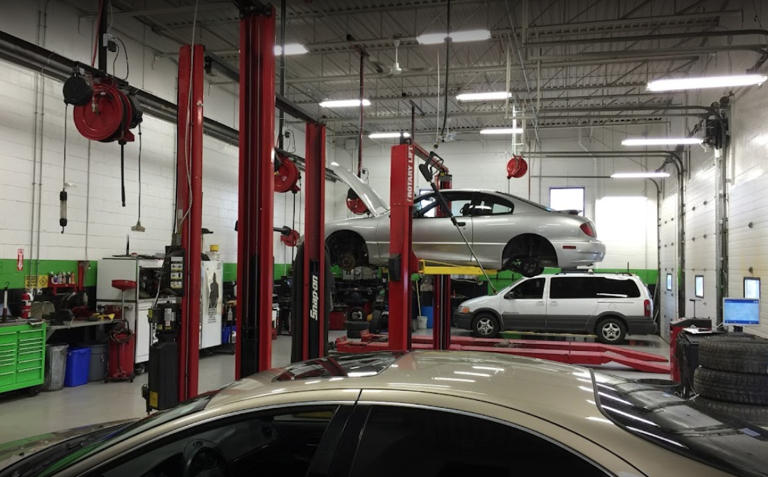 interior of an auto mechanic with a car off the ground with many tools and car parts around on shelves