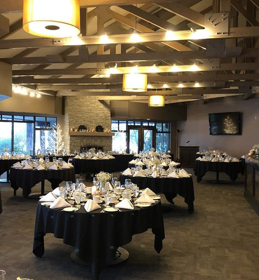 interior of a wedding venue with tables set for dinner with no chairs set in front of a large fireplace