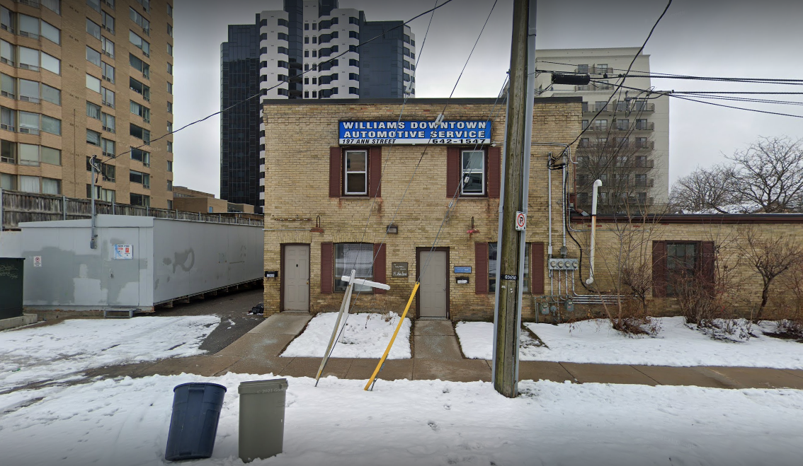 exterior of an auto mechanic building from other side of the sidewalk in winter with snow on the ground