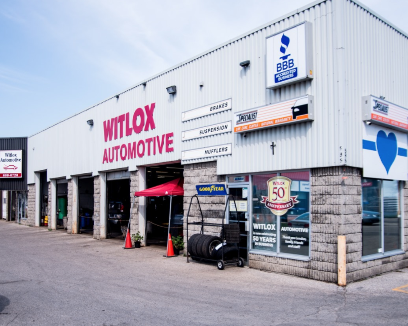 Exterior of an auto mechanic with four garage doors open with cars in bays and a rack of tires sitting to the right on a sunny day
