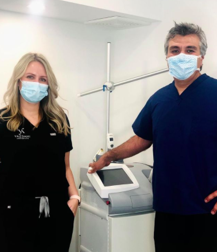 two doctors wearing scrubs and masks standing in front of a medical machine