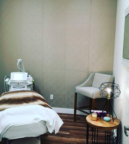 interior of a spa room with a spa bed and chair in the corner with medical machinery in the back left corner