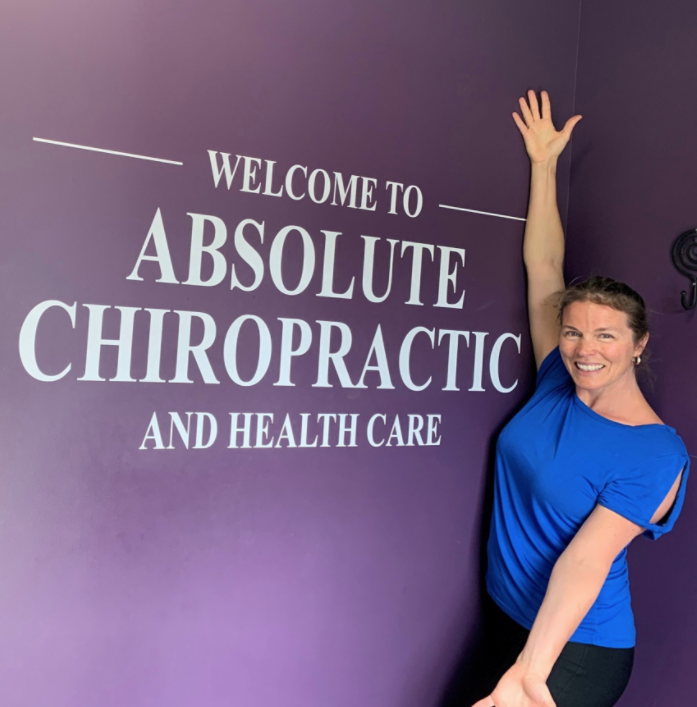 woman standing in front of a business sign with arms open wide