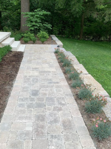 a landscaped backyard with a stone walkway surrounded by small flowers and stone detailing on the right hand side